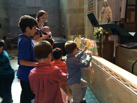 Children collected prayer pledges in baby gift bags and then placed them at the foot of the Blessed Mother's statue