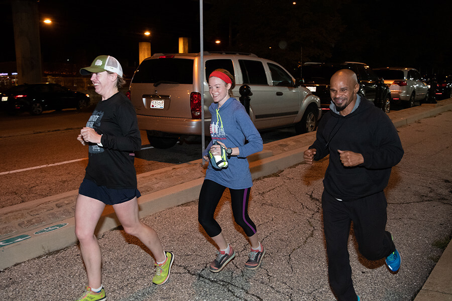 Back On Our Feet runners MaryBeth Nebel, from left, Suzie Brashler and Michael Martin take a pre-dawn run Oct. 15 on Fallsway near Our Daily Bread. (Kevin J. Parks/CR Staff)