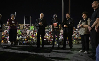 Bishop Mark J. Seitz and Father Fabian Marquez, both of El Paso, Texas, lead prayers Sept. 26, 2019, for Antonio Basco, who lost his wife, Margie Reckard, during the Aug. 3 Walmart mass shooting in El Paso.