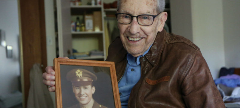 Don Stoulil of Sacred Heart Parish in Robbinsdale, Minn., holds a picture of himself Oct. 30, 2019, which was taken near the end of his tour of duty in World War II as a B-17 bomber pilot.