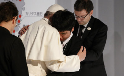 "Pope Francis embraces a young man as he meets with victims of the 2011 ""triple disaster"" (earthquake, tsunami and nuclear power plant meltdown) at Bellesalle Hanzomon, Tokyo, Japan, Nov. 25, 2019."