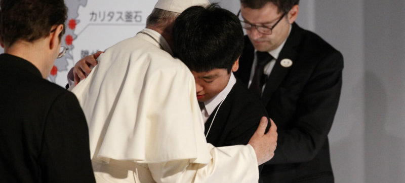 """Pope Francis embraces a young man as he meets with victims of the 2011 """"triple disaster"""" (earthquake, tsunami and nuclear power plant meltdown) at Bellesalle Hanzomon, Tokyo, Japan, Nov. 25, 2019."""